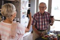 Старшие женщины, нажав фото мужчина на кухне дома — стоковое фото