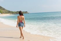 Rear view of woman walking in the beach on a sunny day — Stock Photo