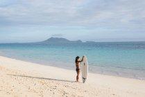 Женщина, стоя с доски для серфинга на пляже в Солнечный день — стоковое фото