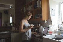 Schöne Frau mit Laptop beim Kaffee in der Küche zu Hause — Stockfoto