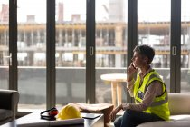Женщина-архитектор разговаривает по мобильному телефону в офисе — стоковое фото
