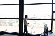 Mature businesswoman with mobile phone looking through window at office — Stock Photo