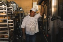 Portrait of male baker standing in bakery shop — Stock Photo