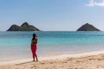 Задній вид жінка, стоячи на пляжі на сонячний день — стокове фото
