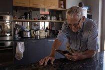 Старший чоловік відеодзвінків цифровий планшетний ПК кухні в домашніх умовах — стокове фото