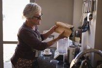Старшая женщина кладет молоко в кофеварку на кухне — стоковое фото