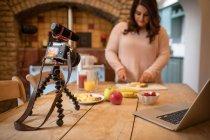 Жіночий vlogger нарізкою фруктів на Розробні рада в домашніх умовах — стокове фото