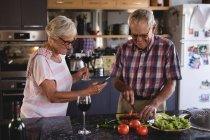 Senior couple cutting vegetables in kitchen at home — Stock Photo