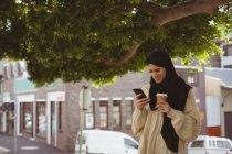 Улыбающаяся женщина хиджаба рассматривает фотографии на мобильном телефоне на улице — стоковое фото