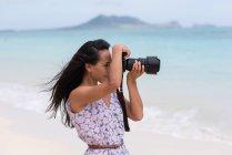 Giovane donna cliccando foto con fotocamera digitale in spiaggia — Foto stock