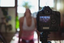 Female video blogger recording video vlog while exercising at home — Stock Photo