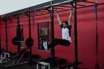 Athlete exercising on monkey bar in a gym — Stock Photo