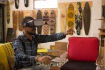 Homem usando fone de ouvido de realidade virtual em oficina — Fotografia de Stock