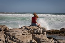 Rear view of woman relaxing on rock at beach — Stock Photo