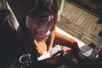 Femme écrivant sur un journal intime dans le salon à la maison — Photo de stock