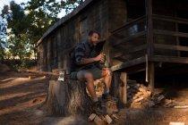 Thoughtful man with water bottle sitting on tree stump — Stock Photo