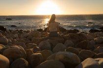 Vue arrière de la femme faisant la méditation sur le rocher au coucher du soleil — Photo de stock