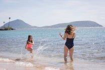 Madre e hija divirtiéndose en la playa en un día soleado - foto de stock
