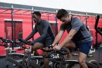 Молодих спортсменів, які здійснюють велотренажери в тренажерний зал — стокове фото
