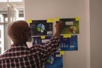 Designer gráfico sênior olhando para notas pegajosas no escritório — Fotografia de Stock