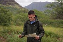 Jovem olhando para o mapa no campo — Fotografia de Stock