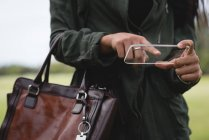 Mid section of woman using glass mobile phone in park — Stock Photo