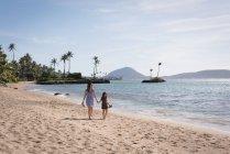 Vista posteriore di madre e figlia che camminano insieme in spiaggia — Foto stock