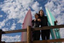 Surferpaar steht an einem sonnigen Tag mit Surfbrett am Strand — Stockfoto