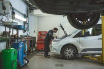 Male mechanic servicing car at repair garage — Stock Photo