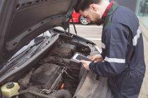 Maschio meccanico usando la tavoletta digitale al garage di riparazione — Foto stock