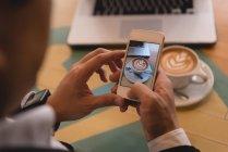 Закри бізнесмен, натиснувши фото кави в кафе — стокове фото