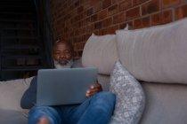 Старший мужчина лежал на диване при использовании ноутбуков на дому — стоковое фото
