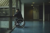 Side view of handicapped man on wheelchair looking out from glass pane — Stock Photo