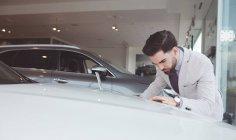 Beau vendeur examinant la voiture au showroom — Photo de stock