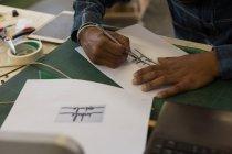 Man making design on paper in workshop — Stock Photo