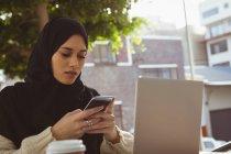 Femme belle hijab à l'aide de téléphone portable au café de la chaussée — Photo de stock
