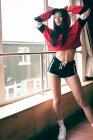 Портрет жіноче танцюрист, стоячи з руки за спиною біля вікна в студії танцю — стокове фото