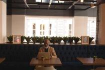 Senior graphic designer using laptop in cafeteria at office — Stock Photo