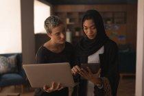 Коллеги по бизнесу используют ноутбук и планшет в офисе — стоковое фото