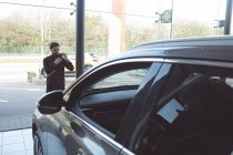 Salesman taking picture of car with mobile phone at the showroom — Stock Photo