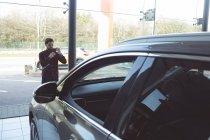Foto de toma vendedor de coche con el teléfono móvil en el showroom - foto de stock
