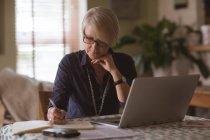 Femme mûre écrivant dans un journal tout en utilisant un ordinateur portable à la maison — Photo de stock
