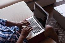 Hombre mayor sentado en el sofá mientras usa el ordenador portátil en casa - foto de stock