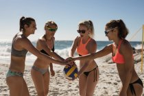 Female volleyball players forming hand stack on the beach — Stock Photo