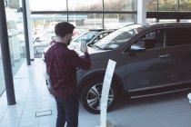 Photo prise de vendeur de voiture avec téléphone mobile à la salle d'exposition — Photo de stock