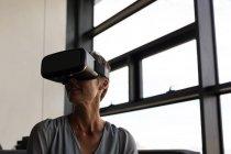 Зрелая деловая женщина, использующая гарнитуру виртуальной реальности в офисе — стоковое фото