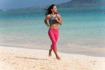 Woman jogging in the beach on a sunny day — Stock Photo