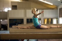 Female athletic balancing on wooden bar at fitness studio — Stock Photo