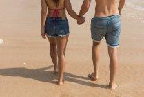 Низький розділ пари разом Прогулянка рука об руку на пляжі — стокове фото