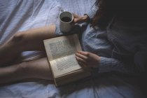 Woman with coffee reading a book on bed at home — Stock Photo